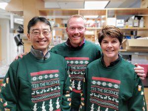 Lab members posing in Science sweater